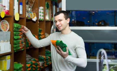 petshop: Portrait of happy guy selecting vet food in petshop