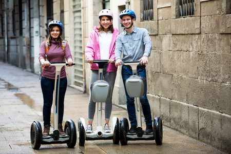 25s: Smiling girls and guy traveling through city by segways