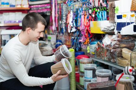 petshop: Portrait of cheerful guy selecting tasty treats in petshop Stock Photo