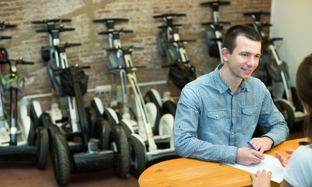 rental agency: Happy young couple selecting segways in rental agency indoors