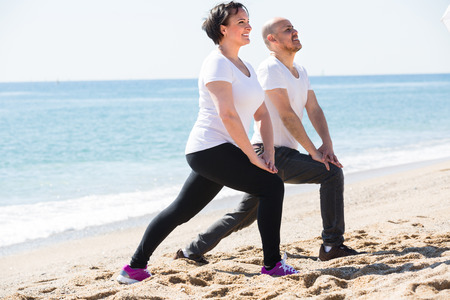 Happy smiling mature couple doing yoga exercises on the sandy beach. Focus on woman Stock Photo