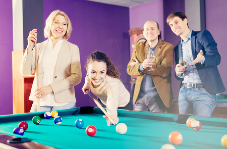 Positive young people playing billiard and darts as hanging out