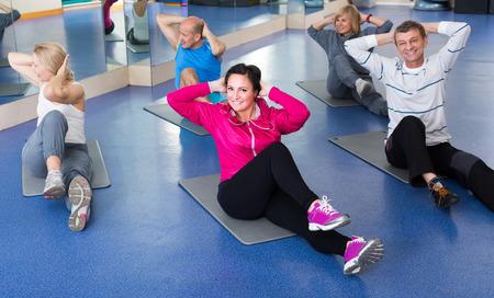 european people: Elderly positive european people training in a gym on sport mats Stock Photo
