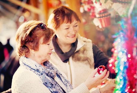 Cheerful female pensioners buying a X-mas decorations at a fair Stock Photo