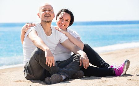 gladly: Pleasant  smiling mature couple gladly hugging each other and enjoying the beach