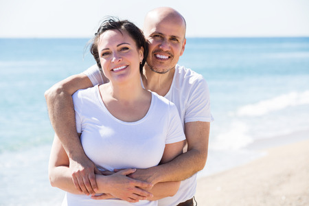 Close-up portrait of a mature man and a woman happily embracing each other on the beach