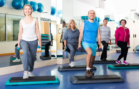 workouts: Mature happy people do pilates in a sport club with dumbbells
