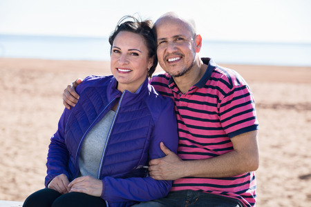 gladly: Cheerful mature couple gladly hugging each other and enjoying the beach