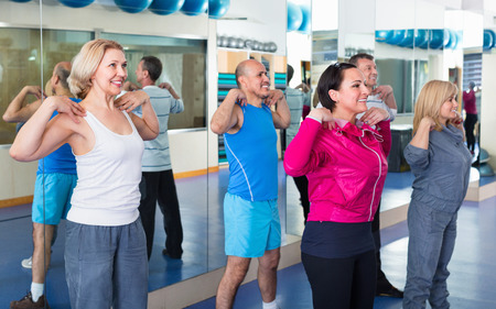 lifestile: Positive friendly smiling people training in a gym doing pilates