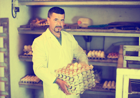 checking ingredients: Serious mature man in white coat holding carton tray with fresh eggs on farm