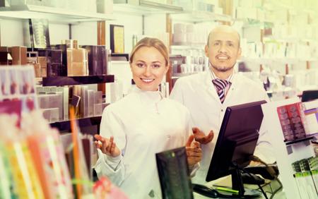 diligente: Dos diligentes farmac�uticos femeninos y masculinos amigables con bata blanca de trabajo del almac�n farmac�utico Foto de archivo