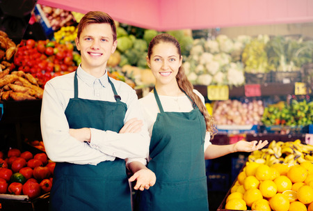 happines: Young european workers selling fresh fruits and vegetables on market Stock Photo