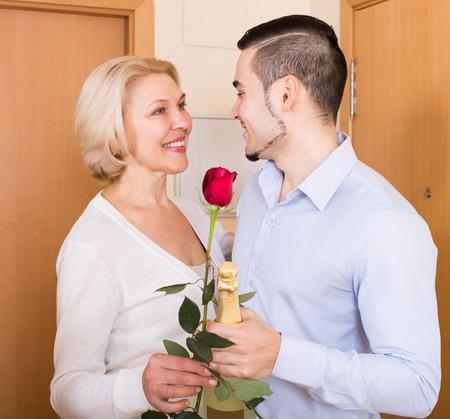 mismatch: handsome man and happy elderly woman standing at doorway Stock Photo