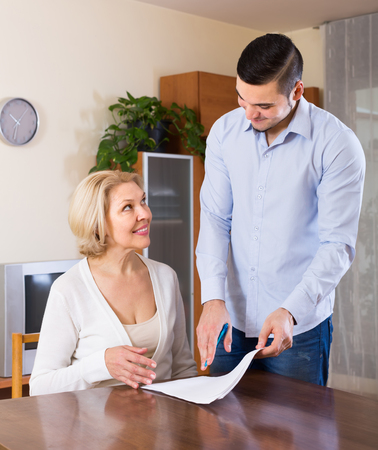 Smiling adult son helping senior mother with documents for buying apartment Stock Photo