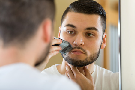 electric razor: Guy looking at mirror and shaving mustache with electric razor