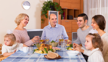 grand child: Multigenerational family sitting at the table set for dinner together Stock Photo