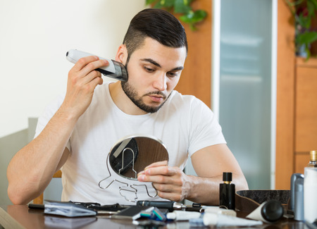 trimmer: young guy looking at mirror and shaving beard with trimmer