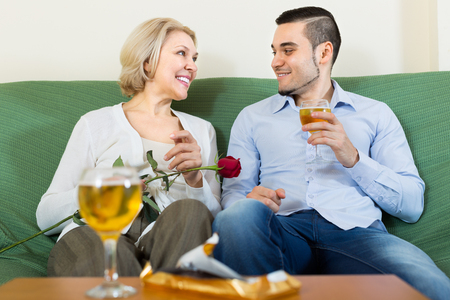 Handsome young guy and elderly blonde woman drinking wine and smiling indoor