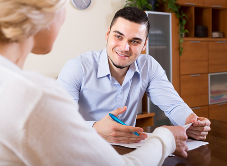 mismatch: Young smiling man and aged woman sitting with banking documents indoors Stock Photo