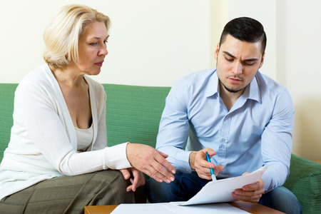 mismatch: Sad elderly woman and young boyfriend with invoices for payment at home