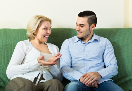 mismatch: Smiling young man and senior woman having pleasant conversation indoor