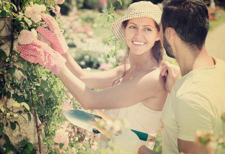 Smiling girl in flowers garden with her boyfriend at summer day