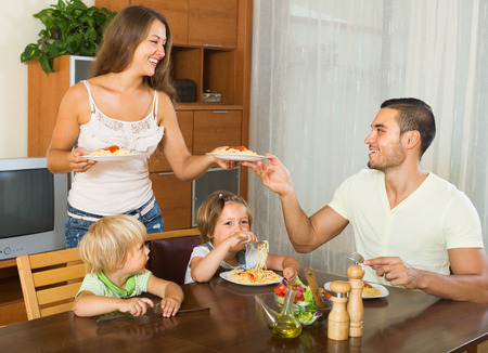 gladful: Happy young parents and two children having lunch with spaghetti at home together
