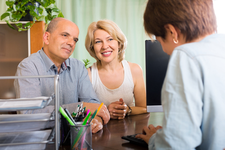 make public: Public notary helping happy smiling couple to make a will in office Stock Photo