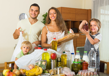provision: Happy smiling young parents with two little kids came back from supermarket