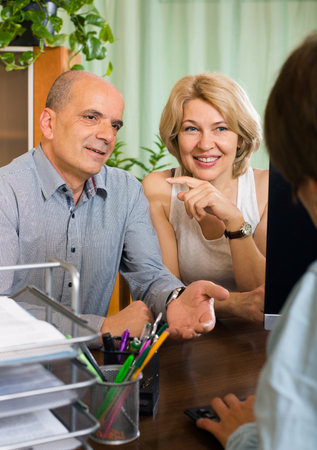 make public: Public notary helping happy mature couple to make a will in office