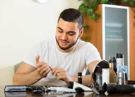 positiv: Handsome young guy cutting nails with cuticle scissors in home interior