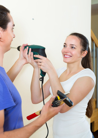 modifying: Positive man and smiling woman drilling wall with drill at home Stock Photo