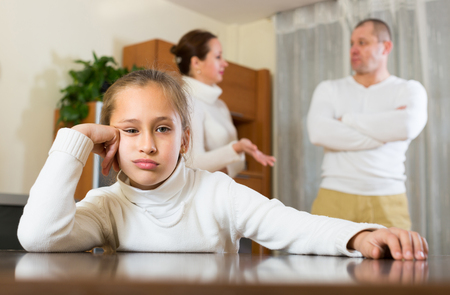 berate: Ordinary adult couple with sad daughter having quarrel at home. Focus on girl