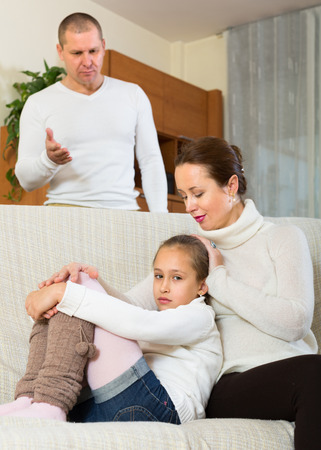 Angry parents berating sad little daughter in home interior. Focus on girl