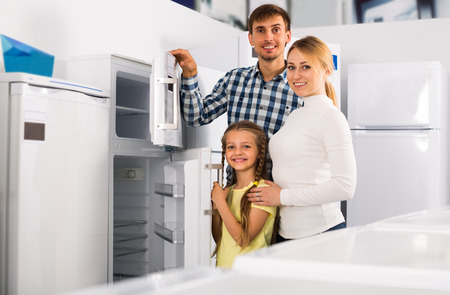 portrait of cheerful family choosing refrigerator in appliance store
