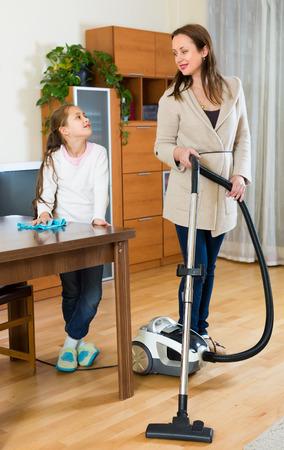 dusting: Schoolgirl dusting and her mother vacuuming in living room. Focus on girl