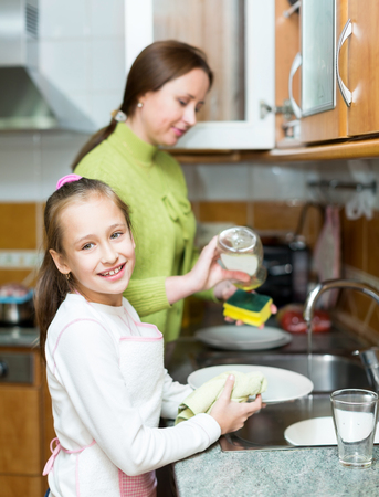 Little girl with mother washing dishes in kitchen Stock Photo