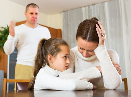 home comforts: Daughter comforting sad mother in livingroom and angry father