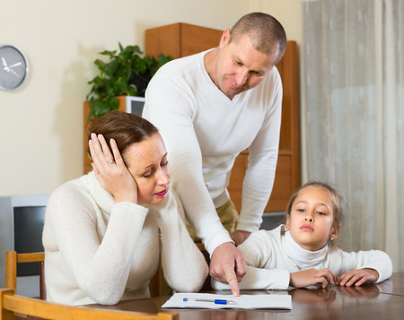 pay bills: Sad family counting money to pay bills at the table at home. Focus on woman