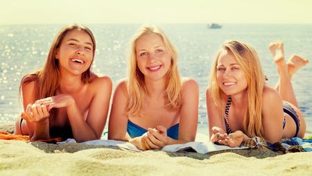 Trois jeunes filles souriantes en maillot de bain couchés ensemble sur la plage. Focus sur toutes les personnes