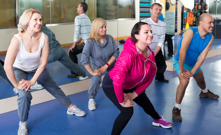 lifestile: Group of happy adults doing aerobics exercise in  sport club