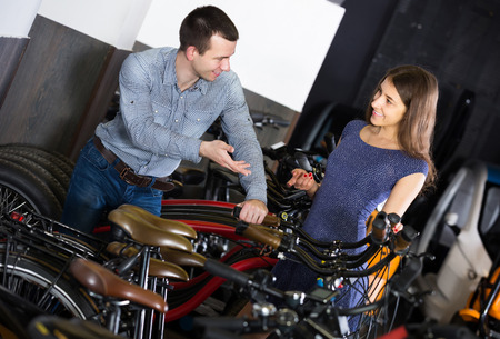 rental agency: smiling american female employee helping adult guy to select bike at rental agency Stock Photo