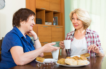 talkative: Two smiling elderly women sitting at the table and talking with cup of tea