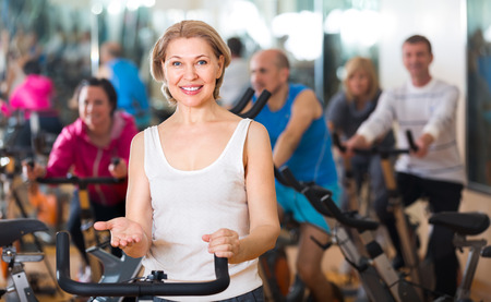 lifestile: Smiling elderly woman on fitness cycle in a gym Stock Photo