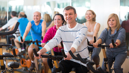 lifestile: Elderly man on fitness cycle in fitness club