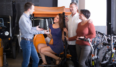 ot: Group of friends hiring grand tour electric ot rental store. Selective focus