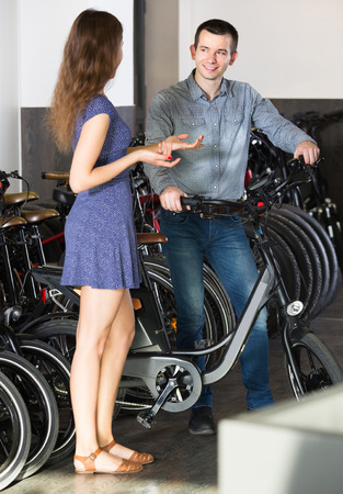 rental agency: Kindly female employee helping smiling adult guy to select bike at rental agency