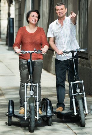 staying: Mature couple staying with an electric bikes outside and smiling. Focus on man