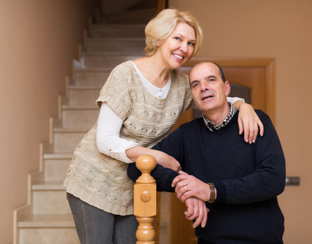 spouses: Smiling elderly spouses leaning against stairway indoor