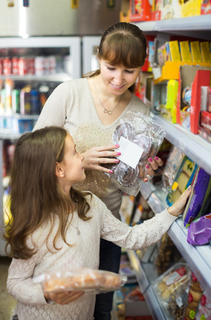clase media: middle class  mother with little girl buying pastry at grocery